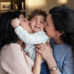 mom and grandma kissing child